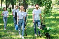 志愿和种植树的愉快的朋友 免版税库存照片