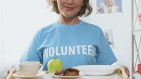 志愿拿着的盘子用免费食物,对低收入或无家可归的人的帮助 股票视频
