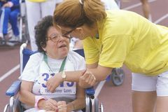 志愿教练的轮椅运动员 免版税库存照片