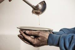 志愿者喂养无家可归者 在一个碗的免费汤叫化子 免版税库存照片