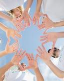 志愿者用一起手反对蓝天 免版税库存图片