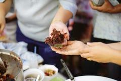 志愿者递交好吃给贫寒:帮助社会的贫寒通过捐赠食物:饥饿的概念 免版税库存照片