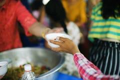 志愿者递交好吃给贫寒:帮助社会的贫寒通过捐赠食物:饥饿的概念 库存照片