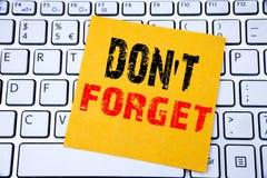 忘记没有 在白色键盘背景的稠粘的便条纸写的提示消息的企业概念 图库摄影