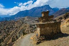 忠实的佛教徒的西藏祷告stupa或祷告地方中心山道路的 背景蓝天 免版税库存图片