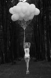 忧郁。有气球的孤独的妇女在黑暗和阴沉的森林里 免版税库存照片