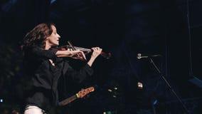 快乐和微笑的女孩小提琴手在舞台使用 凉快和职业音乐家 股票录像