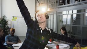 快乐和愉快的商人在旁边有效地跳舞,当在办公室的听的音乐同事时 他佩带 股票视频