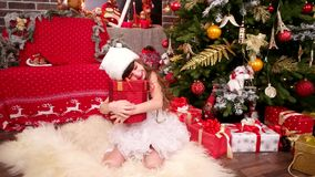 快乐和愉快的小女孩从圣诞老人,新年有圣诞树的` s室接受了礼物 影视素材