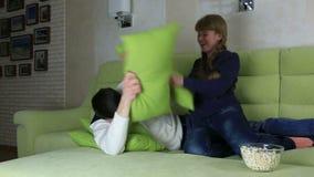 年轻快乐在长沙发的夫妇战斗的枕头 股票录像