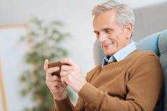 快乐地微笑快乐的年长的人看智能手机和 图库摄影