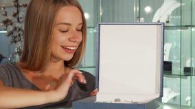 快乐地微笑,当购物在珠宝店时的愉快的妇女 股票录像