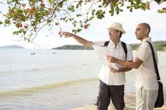 快乐夫妇在度假指向目的地的 库存图片