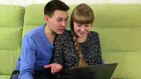 年轻快乐夫妇谈话在膝上型计算机的Skype 影视素材