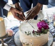 快乐夫妇递切口婚宴喜饼 免版税库存图片
