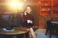 快乐女性叫与巧妙的电话,当坐在现代餐馆内部时 库存照片