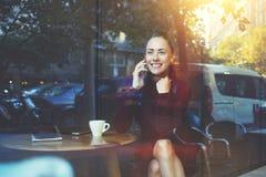 年轻快乐女性叫与手机,当坐在咖啡店时 库存照片
