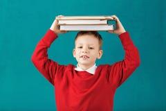 快乐微笑有大书的一点男生在他的头ha 免版税图库摄影
