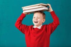 快乐微笑有大书的一点男生在他的头ha 库存图片