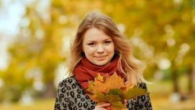 快乐摆在与五颜六色的叶子花束的照相机的一个女孩  在城市公园走在秋天 免版税图库摄影