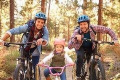 快乐男性加上循环通过秋天森林地的女儿 免版税图库摄影