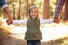 快乐男性加上走通过秋天森林地的女儿 免版税图库摄影
