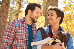 快乐男性加上走通过秋天森林地的婴孩 库存照片