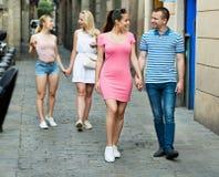 快乐的上散步的男人和妇女在欧洲镇 免版税库存图片