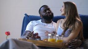 快乐的不同的夫妇吃早餐在床 股票录像