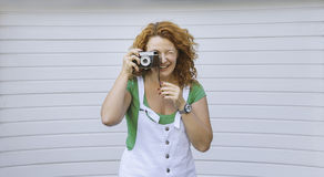 快乐的中部使用葡萄酒照相机的年迈的夫人 天,室外 拍在减速火箭的照相机的愉快的红色头发妇女照片 免版税库存照片