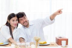 快乐的亚裔年轻谈话人和的妇女吃坐的午餐和一起指向某事 库存照片