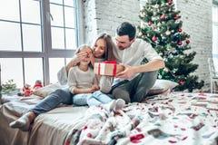 快乐的交换礼物的母亲、父亲和她逗人喜爱的女儿女孩 父母和小孩获得乐趣在圣诞树附近 免版税库存照片