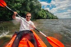 快乐的人在红色皮船和行坐与桨 免版税图库摄影