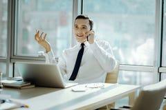 快乐的人有一次宜人的电话交谈在办公室 免版税库存照片