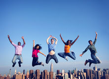 快乐的人民跳跃的友谊幸福城市概念 免版税库存图片