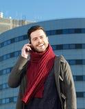 快乐的人谈话在手机在城市 免版税库存图片