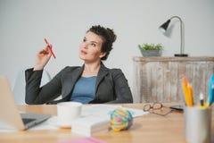 快乐的企业夫人在办公室工作 库存照片