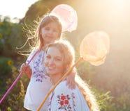 快乐的使用在与昆虫的一个领域的母亲和她的女儿 库存照片