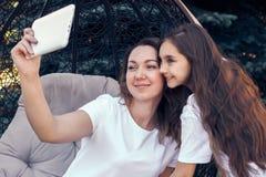 快乐的做selfie照片的母亲和女儿由片剂个人计算机 库存照片