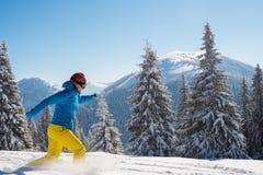 快乐的冒险家,妇女在冬天山跑 免版税库存图片