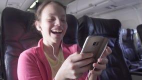 快乐的十几岁的女孩打在智能手机的一场比赛在飞机的客舱,当旅行的储蓄英尺长度录影时 股票录像