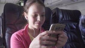 快乐的十几岁的女孩打在智能手机的一场比赛在飞机的客舱,当旅行的储蓄英尺长度录影时 影视素材