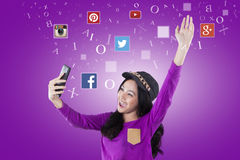 快乐的十几岁的女孩拿着有社会媒介商标的手机 免版税库存图片