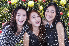 快乐的十几岁的女孩有圣诞树背景 免版税库存照片