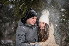 快乐的十几岁获得乐趣在多雪的森林 免版税库存照片