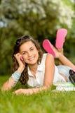 快乐的叫学生女孩说谎的草电话 免版税库存照片