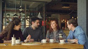 快乐的可爱的小姐讲滑稽可笑的故事给她的朋友在咖啡馆的午餐,人们笑和 影视素材