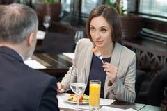 快乐的同事开一次会议在餐馆 免版税库存图片