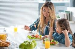 快乐的品尝新鲜的切好的菜的母亲和孩子 免版税库存照片