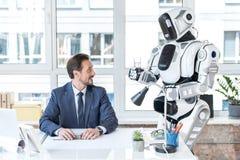 快乐的商人在有机器人的办公室劳动 免版税库存照片